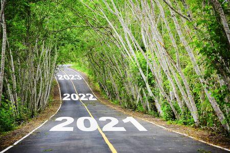 Tunnel d'arbres avec 2021 à 2023 sur la surface de la route asphaltée, concept de bonne année et idée naturelle