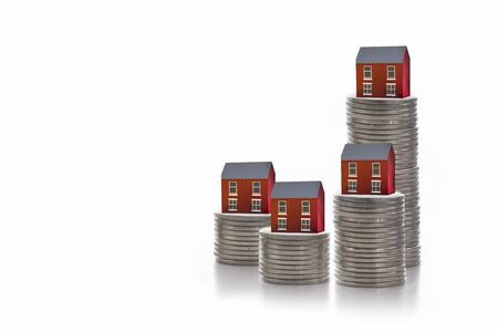 House model on stack of coins on white background, mortgage and real estate investment concept Standard-Bild