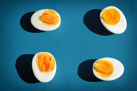 Boiled egg with shadow on blue background, abstrat and pattern concept