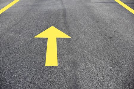 Yellow arrow on asphalt road surface, transportation concept and keep moving idea