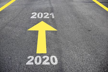 New year 2020 to 2021 on asphalt road surface with arrow, Business challenge concept and keep moving idea