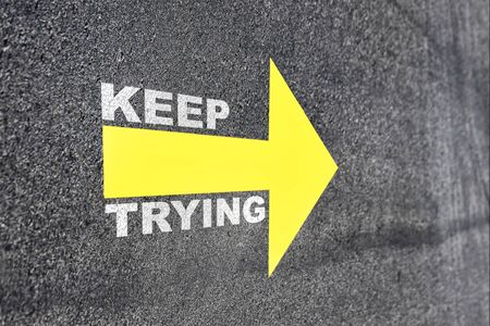 Keep trying word with yellow arrow on road, Business challenge concept and keep moving idea
