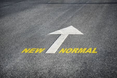 Words of new normal with white arrow marking on road surface, transportation concept and business challenge idea Фото со стока