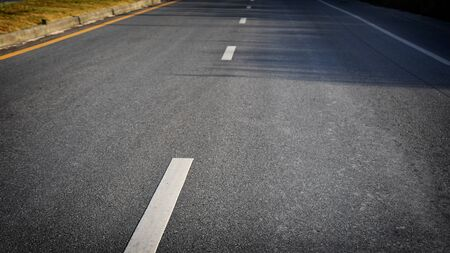 White dividing lines on black asphalt road surface with sunlight, transportation concept and road trip idea