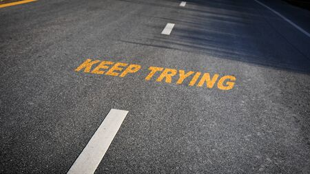 Keep trying word with white dividing lines on black asphalt road surface with sunlight, business challenge concept and effort idea