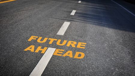 Future ahead word with white dividing lines on black asphalt road surface with sunlight, business challenge concept and effort idea