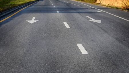 White arrow and dividing lines on black asphalt road surface, transportation concept and road trip idea