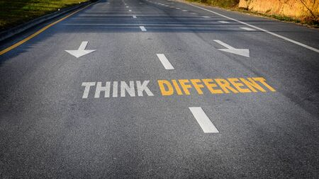 Think different word with white arrow and dividing lines on black asphalt road surface, business challenge concept and success idea