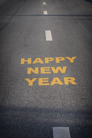 Happy new year words on asphalt road surface with white marking lines