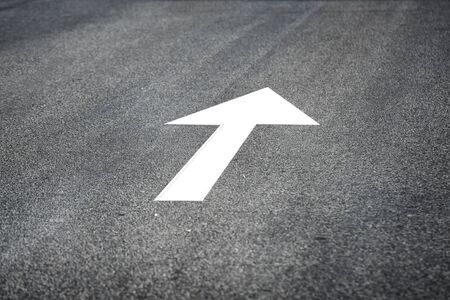 White arrow marking on road surface, transportation concept and business challenge idea