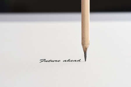 Future ahead word with pencil on white paper on black background, business challenge concept and leadership success idea