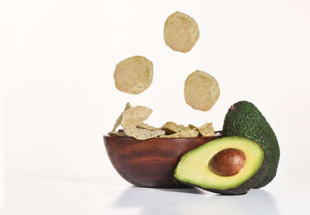 Crispy avocado chips on wooden bowl with fresh avocado fruit on white background, vegetarian concept, fast and quick food idea