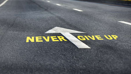 Never give up word with white arrow and dividing lines on black asphalt road, business challenge concept and effort idea Stock Photo