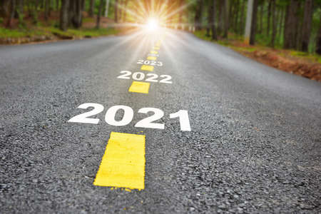 New year journey 2021 to 2024 on asphalt road surface with marking lines and sunlight. Business challenge concept and natural background idea