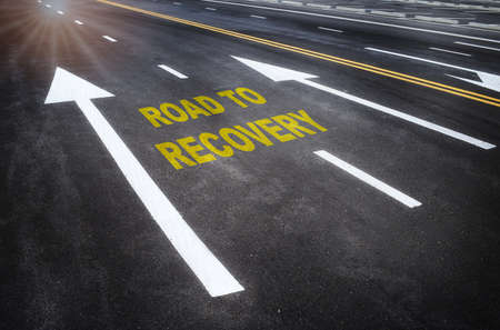 Road to recovery word on road with white arrow. Business cycle stage concept and business challenge idea