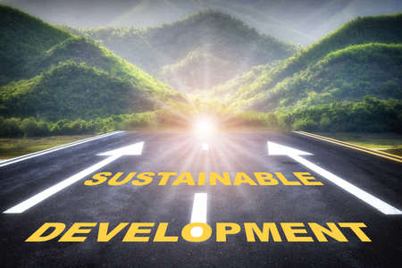 Sustainable development words with white arrow sign marking on road surface for giving directions on mountain background. Sustainability industry, ecosystem and healthy environment concept background Stock fotó