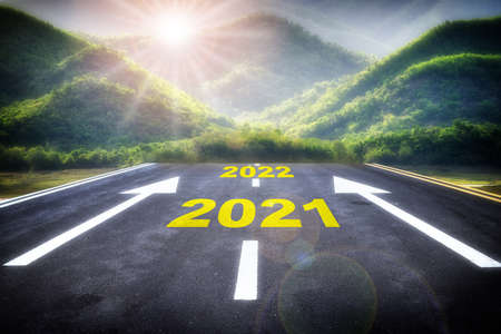 Journey to dream big new year 2021 to 2022 on asphalt with white arrow and mountain nature background. Future ahead concept and business challenge idea Stock fotó