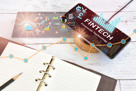 Future of financial technology. New normal after COVID-19 crisis concept and work anywhere idea. Fintech technology on smart phone screen on wireless charger with note book on desk
