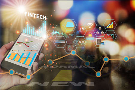 Fintech technology on smart phone screen on city life with new normal word on road background. Future of financial technology concept and new normal after COVID-19 crisis with work anywhere idea. Stock fotó