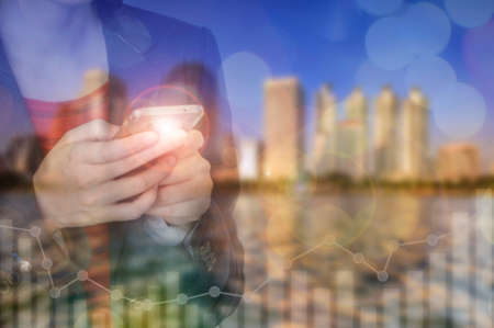 Businesswoman using smart phone on cityscape background. Technology for investment concept and double exposure idea