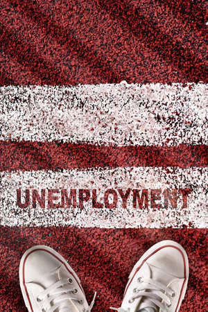 Unemployment word on starting line with white sneaker on red sport track. Social issue concept and challenge idea