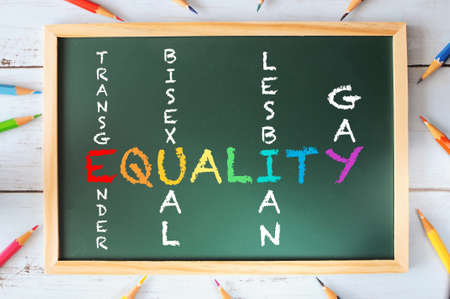 Colorful of equality, transgender, bisexual, lesbian, and gay words on blackboard with colored pencil on wooden background. LGBT concept and social issue idea