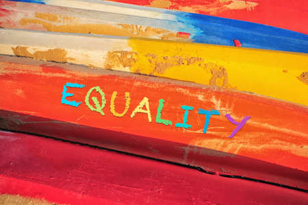 Equality word on colorful side view of kayak boat with sand. Social issue concept and LGBT idea