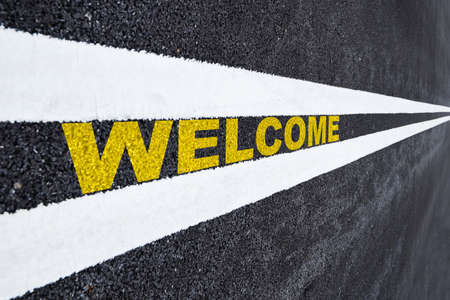 Welcome word written on asphalt road. Business beginning concept and keep going idea