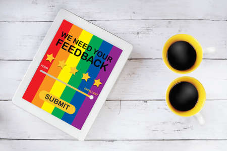 LGBT business rating application review on computer tablet with cup of coffee on table. Five stars feedback concept and business success technology idea Standard-Bild