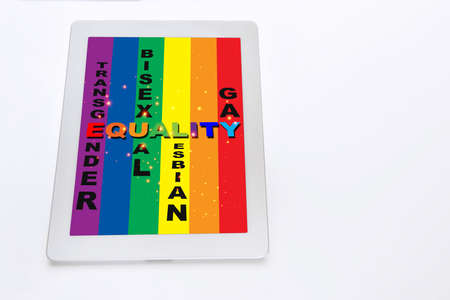 Equality, transgender, bisexual, lesbian, and gay words on rainbow flag on computer digital tablet screen. Social issue concept and LGBT idea