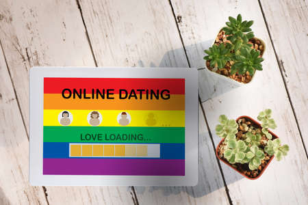 LGBTQ online dating application on computer digital tablet screen with cactus and succulents plant on wooden white background. Online technology concept and digital transformation idea