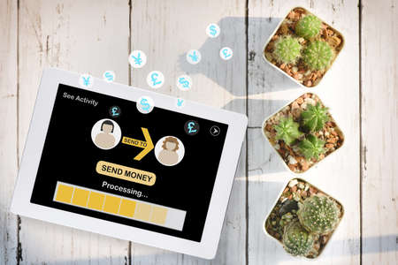 Flat lay mobile banking fintech on smart phone or digital tablet with cactus and succulents plant on wooden white background. Financial technology concept and peer to peer transfer money idea.