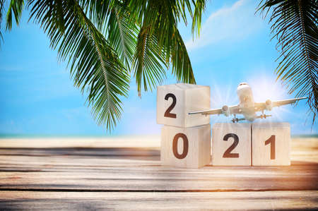 Wood cube number 2021 and commercial plane on planks on tropical beach background, happy new year concept and business transportation idea