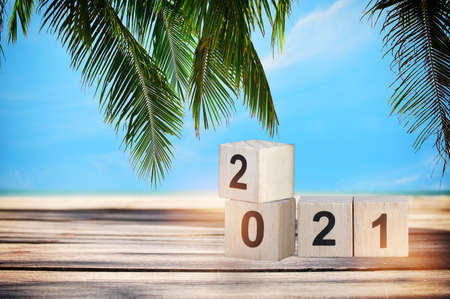 Wood cube number 2021 on planks on tropical beach background, happy new year concept and summer holiday vacation idea