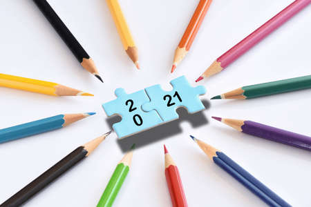 New year 2021 on blue puzzle with colored pencils isolated on white background. Business teamwork concept and synergy connection idea