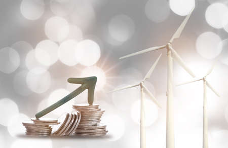 Renewable clean energy investment for sustainability concept and alternative energy economic growth idea. Arrow upwards on stack of coins on bokeh background