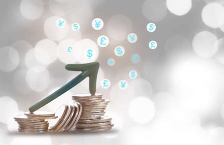 Arrow upwards on coins with currency symbol on bokeh background. Business saving concept and economic recovery and growth idea