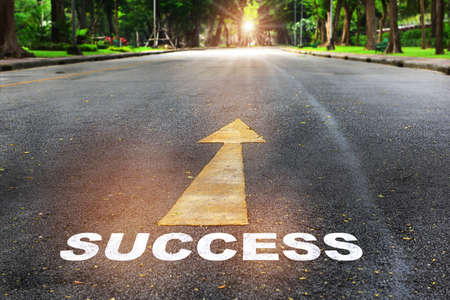 Success word written on the road with arrow on nature background with sunlight. Business planning concept and new year beginning success idea