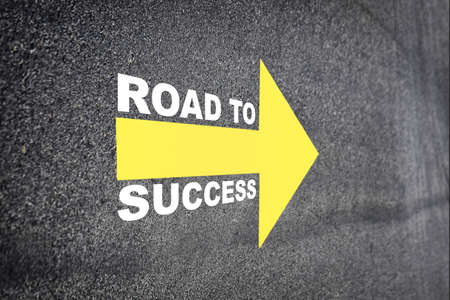 Road to success with yellow arrow marking on road surface.  Transportation concept and business challenge idea Standard-Bild