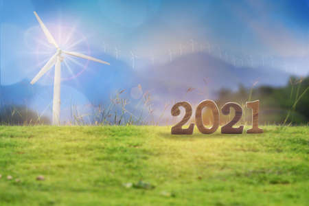 New year 2021 on grasses with wind turbines on mountain background. Renewable clean energy investment for sustainability concept and alternative energy economic growth idea