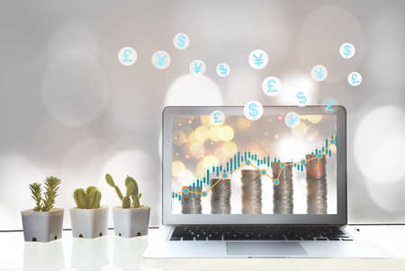 Forex exchange business concepts and return on investment idea. Stack of coins with stock growth graph on computer screen on working desk with currency symbol background