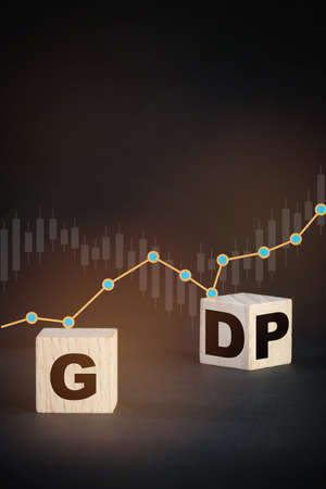 GDP gross domestic product concept and economic recovery idea. GDP written on wooden cube with growth graph on black background