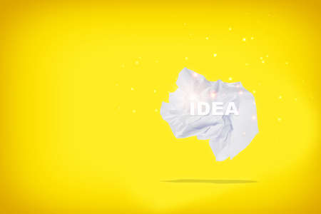 Idea word on white crumpled paper with shadow on yellow background. 版權商用圖片
