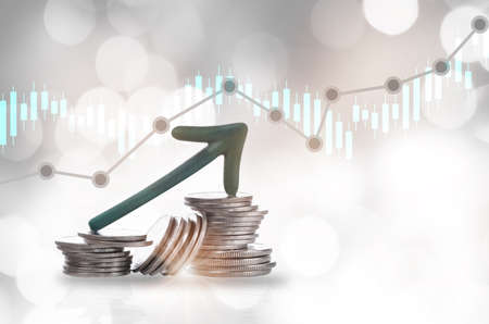 Green arrow upward on stack of coins and growth graph on bokeh background. Economic recovery concept and return on investment ROI idea
