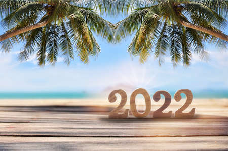 2022 written on wooden cube on planks on tropical beach background, natural bakground concept and happy summer holiday idea Stock fotó