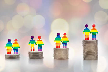 LGBT lesbian gay bisexual transgender rainbow model on stack of coins on colorful bokeh background. Making money with saving concept and return on investment roi idea Stock fotó