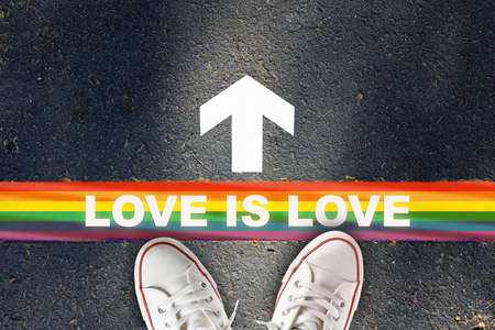 Love is love written on rainbow line marking with white arrow sign with on asphalt road. Lesbian gay bisexual transgender concept and equality diversity idea
