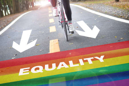 Equality written on rainbow flag marking on road with white arrow sign. Lesbian gay bisexual transgender concept and equality diversity idea Reklamní fotografie