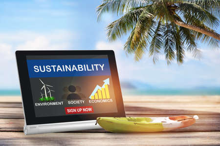 Sustainability environment protection society and economics on computer tablet screen with boat kayak on planks on tropical beach background. Sustainable development concept and smart technology idea Reklamní fotografie - 164995031
