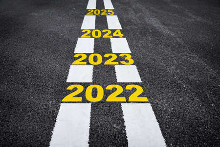 Number of 2022 to 2025 on asphalt road surface with marking lines. Happy new year concept and keep moving idea Reklamní fotografie